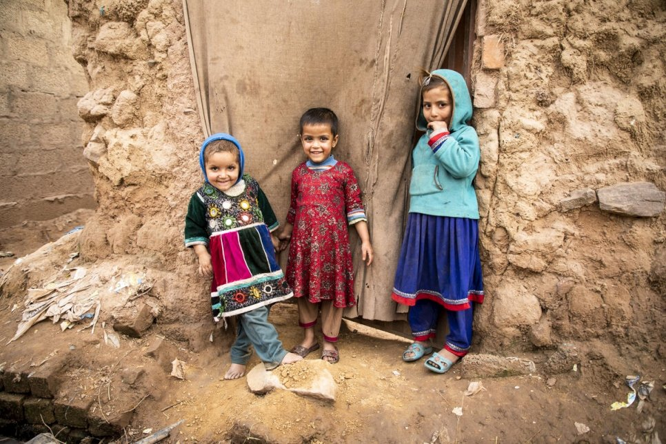 Afghan children stand in a doorway at a settlement in Islamabad, Pakistan, that is home to about 3,000 Afghan refugees. © UNHCR/Roger Arnold