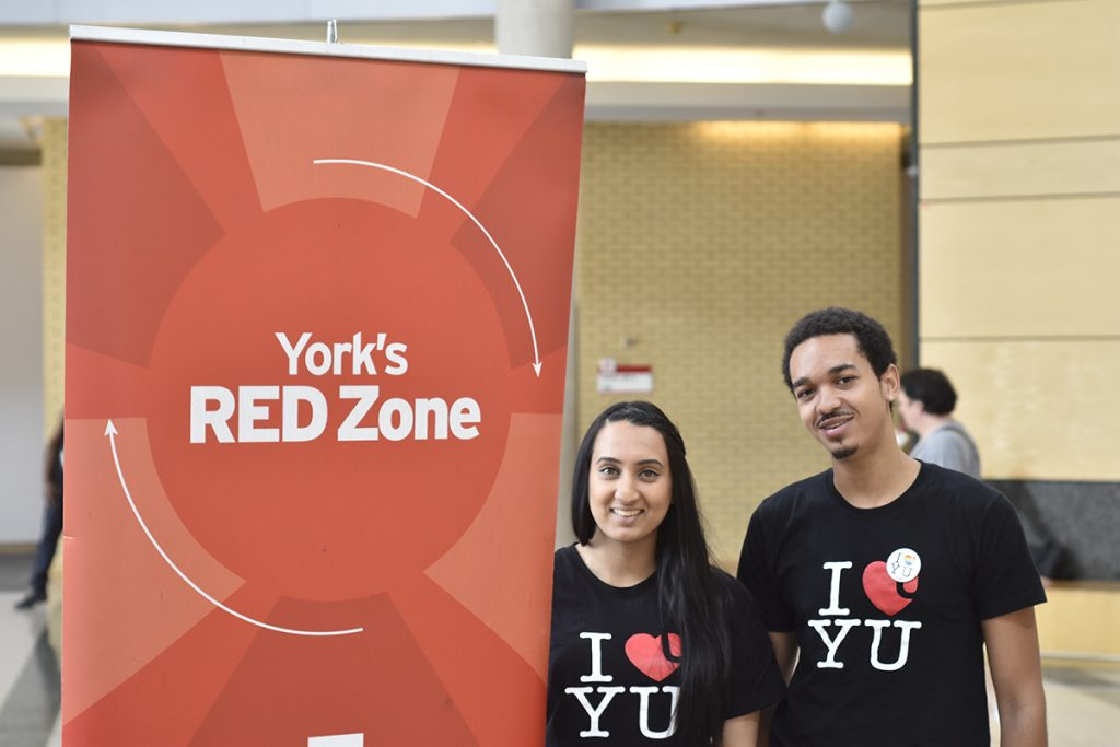 """A young woman and young man beside a banner with the words """"York's RED Zone"""""""