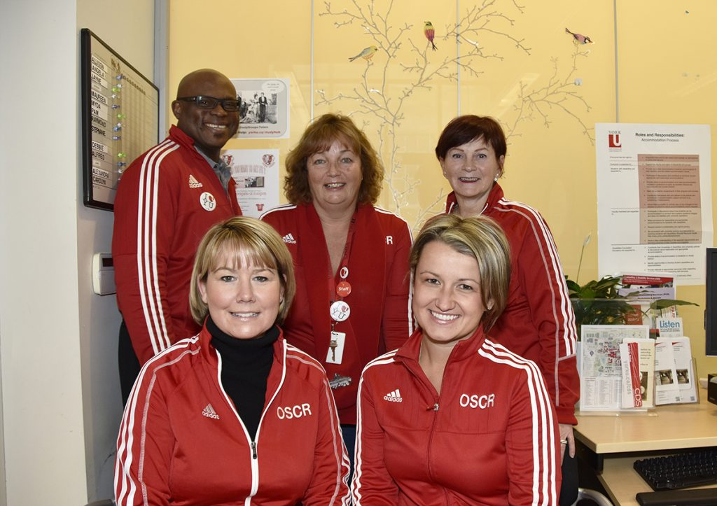 A group photo of all the staff members at OSCR, all wearing red jackets.