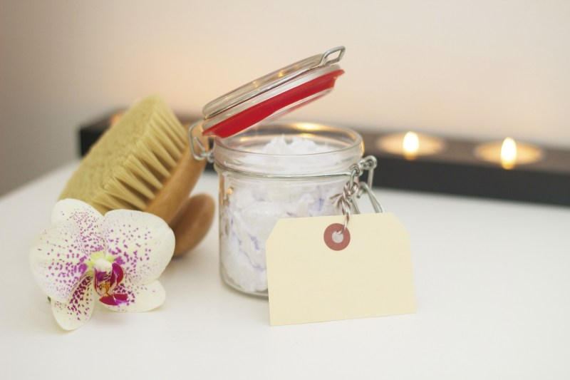 A photo of bath salts, candles, a flower, and a body brush.