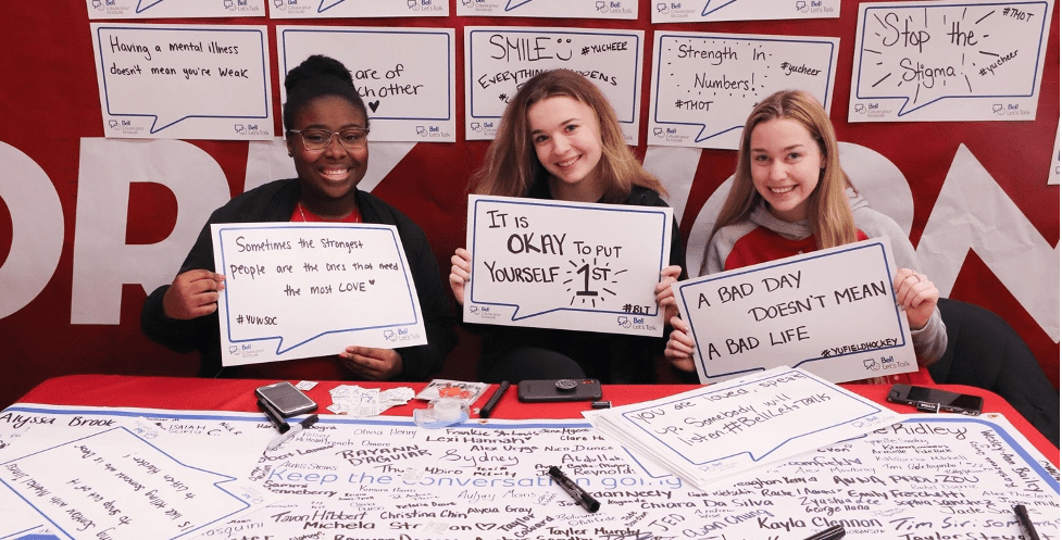 York students holding up positive mental health message posters