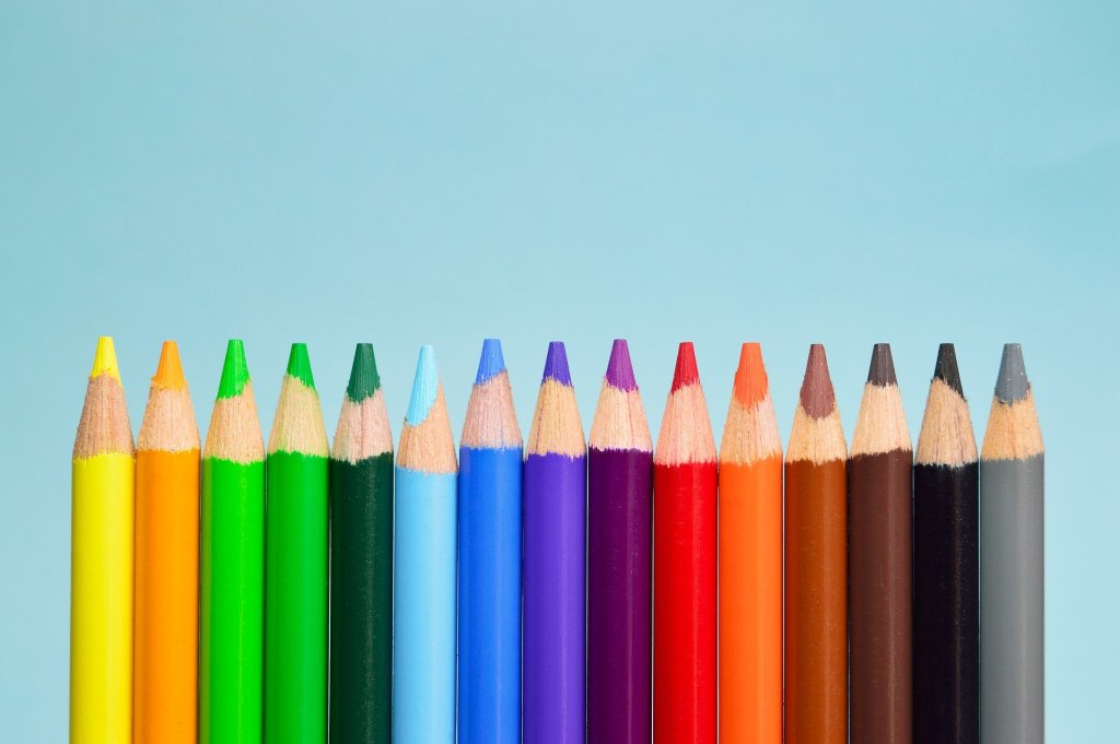 A line of coloured pencils with a blue background