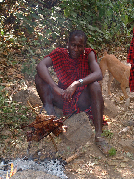 Masai man cooking meat