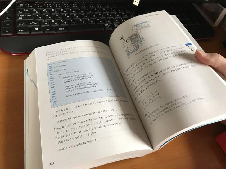 プログラミングの本を片手で持つ