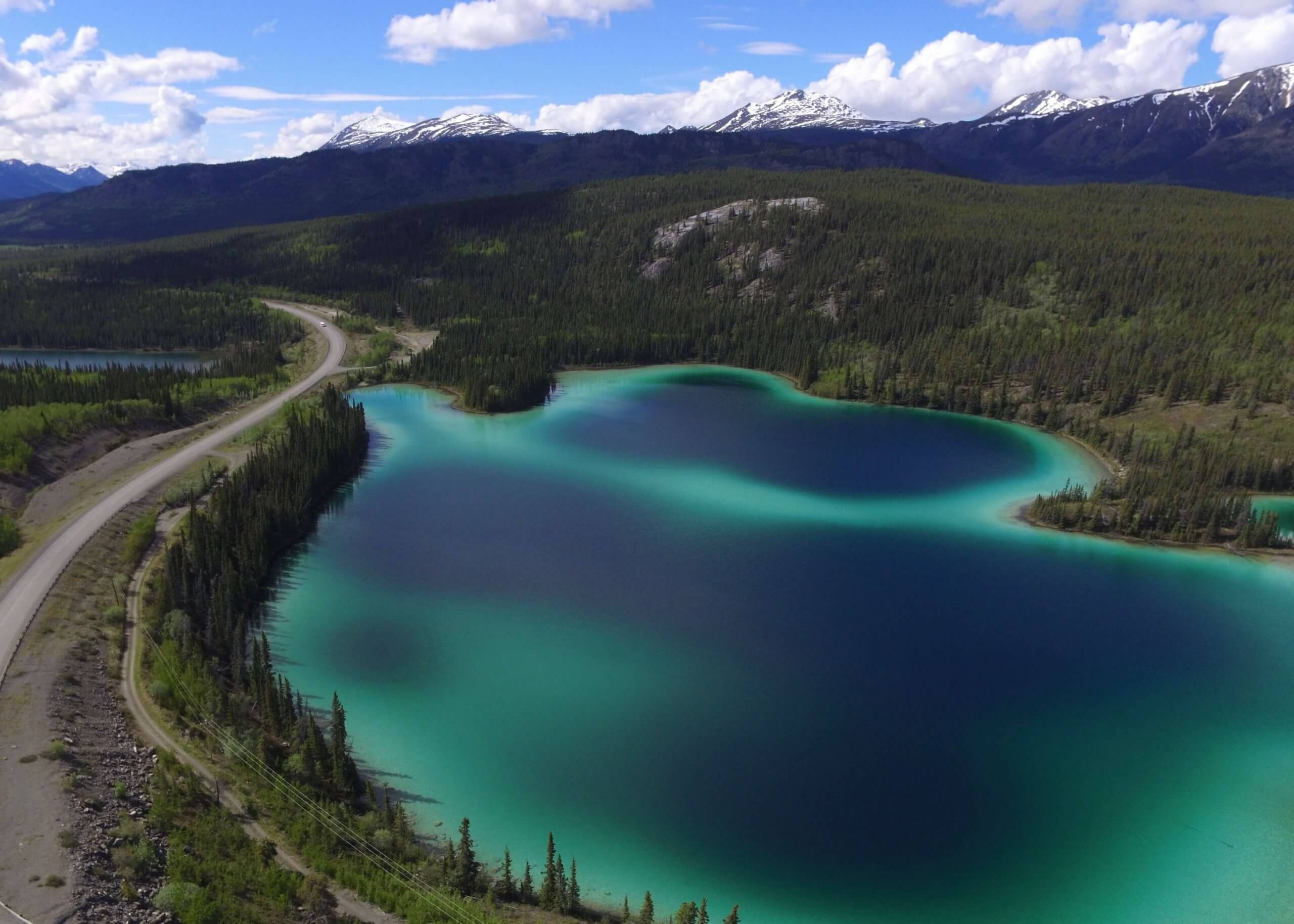 Aerial view of the highway, mountains, and blue and green waters of Emerald Lake, Yukon