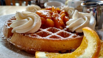 Belgian Waffle with fresh peach fruit compote with whipped cream - Warm, crunchy on the outside, soft on the inside.