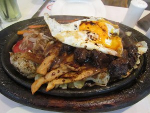 mixed meat sizzler with egg on top & veggies beneath