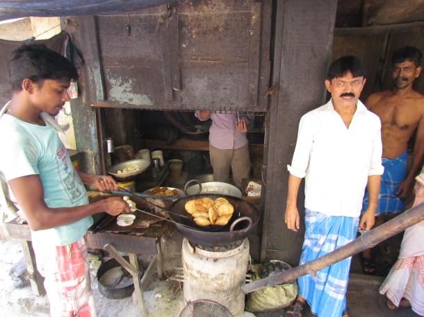 Siraz (white shirt) meeting customers outside his shop