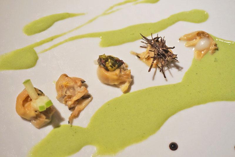 Ostra con salsa de hinojo, ajo negro, manzana verde, algas, champiñón, destilado de tierra y anémonas. Menú Degustación Festival 2018 de El Celler de Can Roca