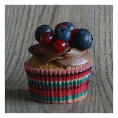Heller Victoria Sponge Cupcake mit einer dunklen Schokoladen Creme verziert mit Blaubeeren und Johannisbeeren.
