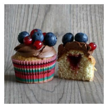 Heller Victoria Sponge Cupcake mit einer Schokocreme veriert mit einem BeerenMix. Ein weiterer Cupcake ist mittig aufgeschnitten und zeigt den Johannisbeerkonfitürekern in der Mitte des Cupcake.