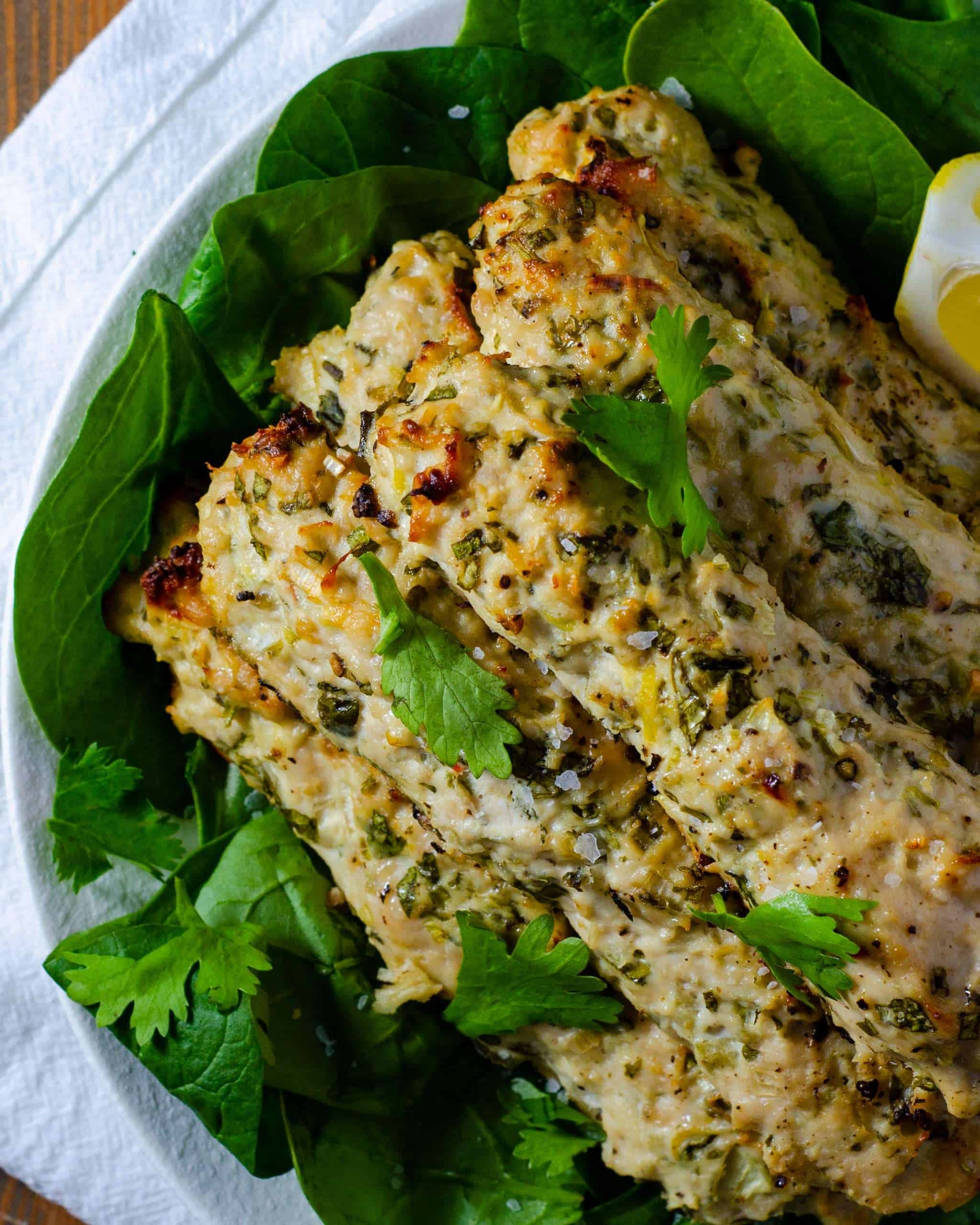 Stack of low carb chicken kebabs on a bed of spinach