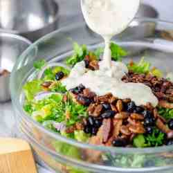 Keto Caesar Salad being dressed in a glass salad bowl