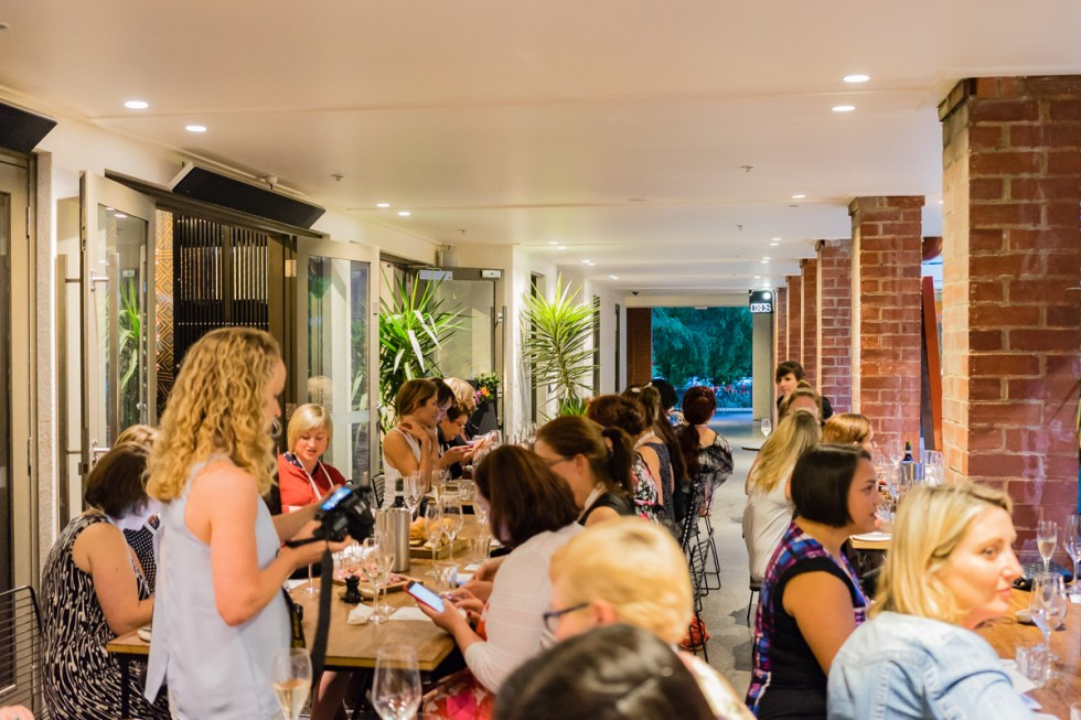 This is a photograph of some of the bloggers sitting at tables on an outside terrace at A.Baker for Eat Drink Blog 6