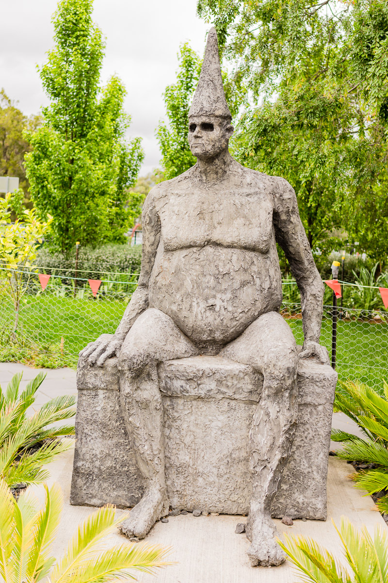 This is a photograph of a sculpture of a fat man with man boobs and big belly. Nissi Gallery Public Art making man boobs fashionable in Canberra.