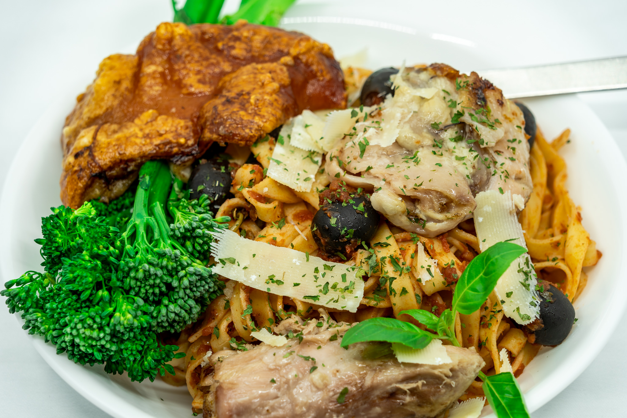 Slow-cooked pork knuckle with fresh egg fettuccine, tomato sauce and steamed broccolini