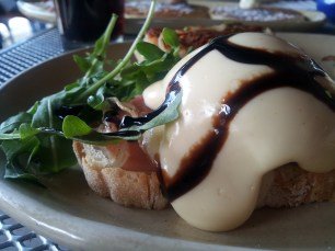 Thin slices of prosciutto, Taleggio cheese, and perfectly poached eggs on toasted ciabatta, topped with cream cheese hollandaise, balsamic glaze and arugula