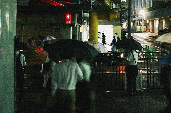 傘を持った信号待ちの人たち