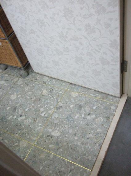 建具もクロスサンゲツフロアタイルの洗面脱衣室金の目地棒
