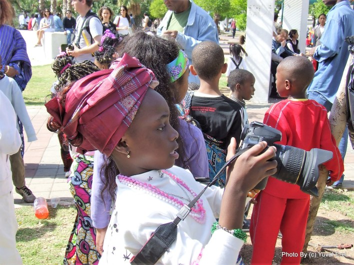 בת מהגרים מתלהבת ממצלמת אחד המתנדבים. צילום יובל אראל