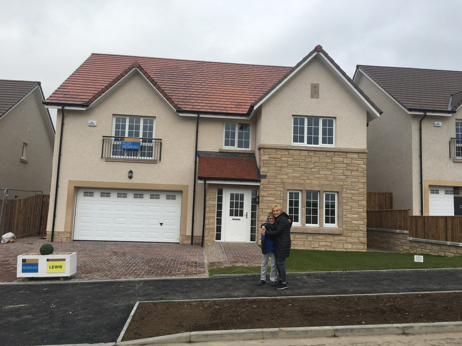 mum and son in front of new home