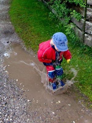 Moritz springt mit Anlauf in die Pfütze