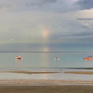 Doesn't it look beautiful, the rainbow which is mirrored in the calm sea surface?