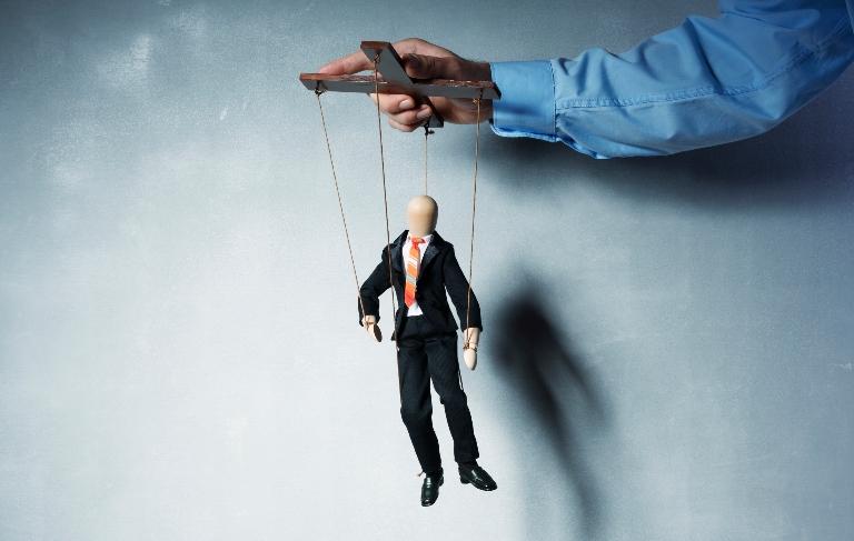 Hånd som holder marionettdukke.