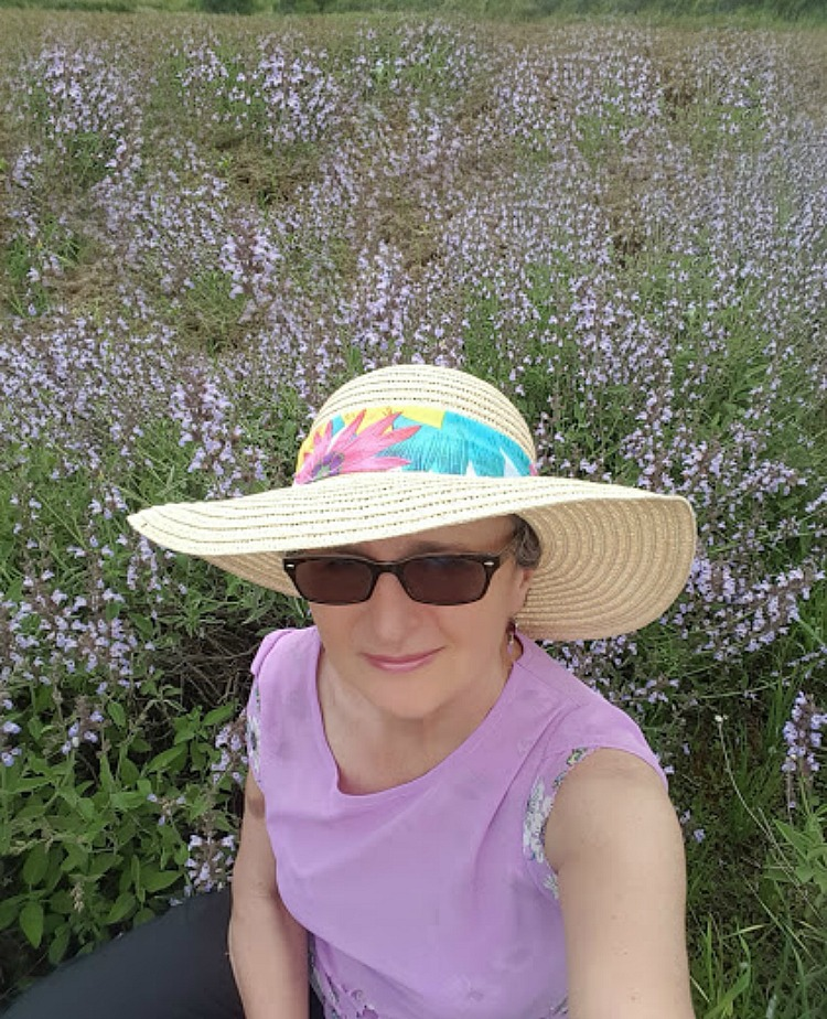 Living and traveling with cancer. Summer hat and meadow.