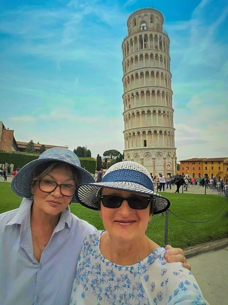 Two sisters visiting in front of leaning tower of Pisa.