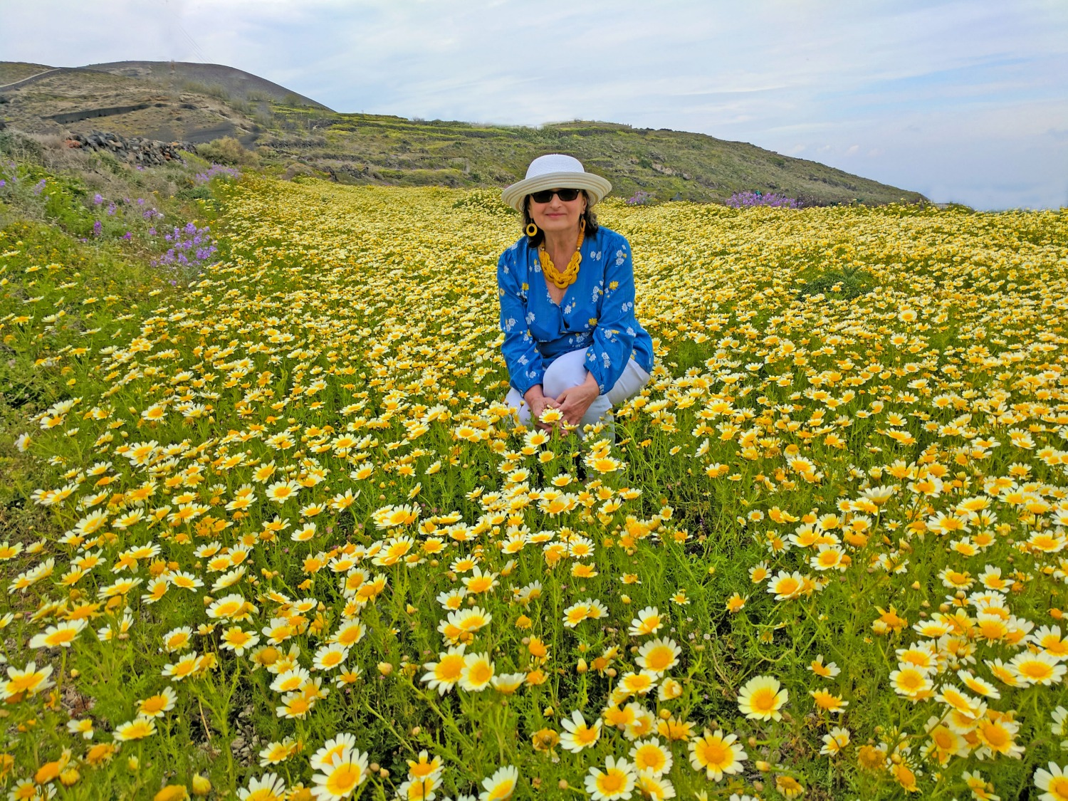 A lady in blue in sea of wildflowers along a hiking trail in Santorini Greece.