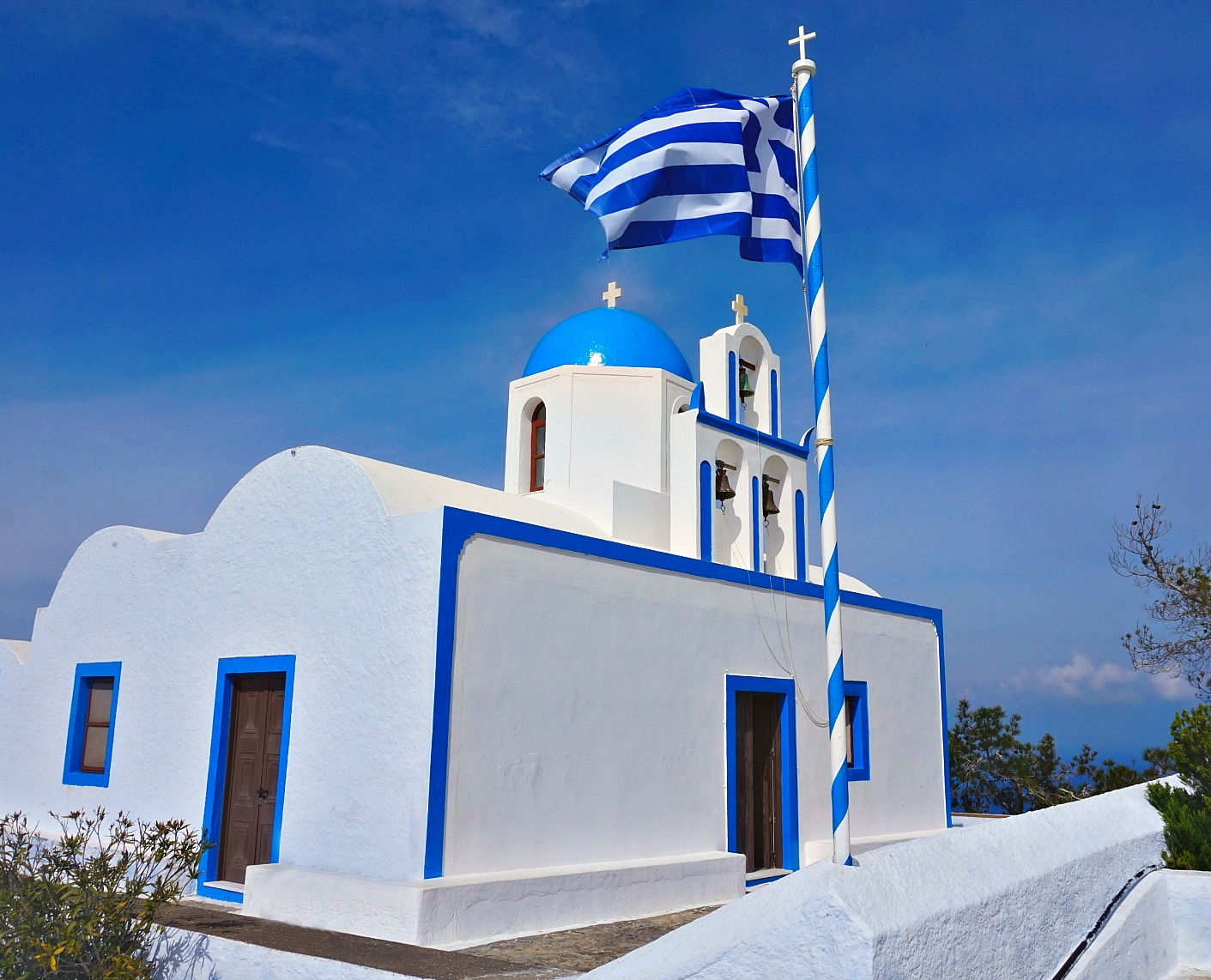 Blue domed church in Santorini next to the Greek flag.