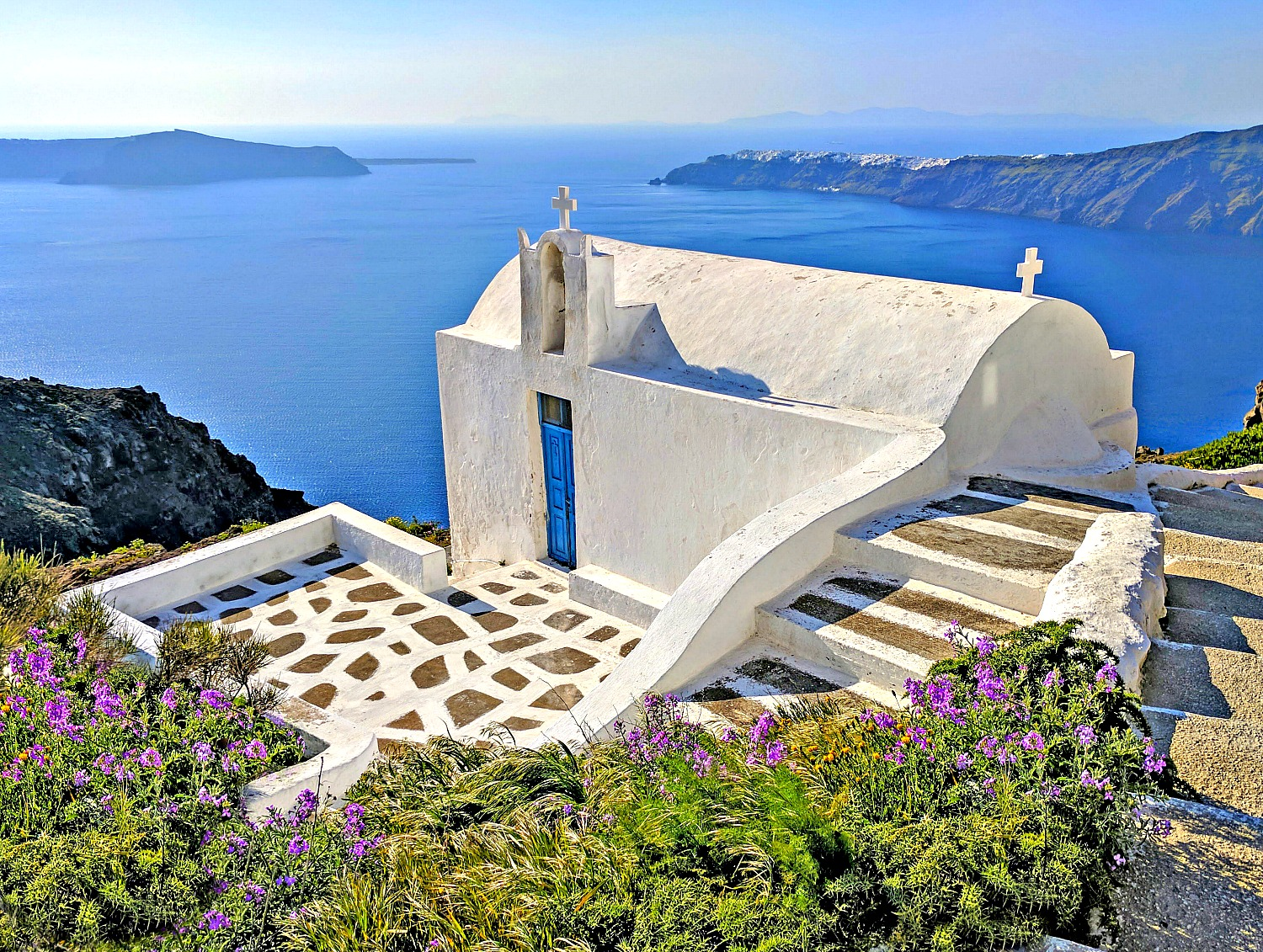 Entering hiking trail to Skaros Rock - sea, church and flowers.