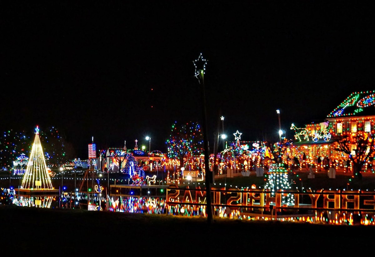 A distant view of Koziar's Christmas Village from the road, with its reflection in a pond.