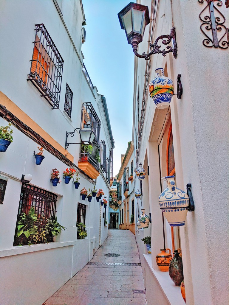 Beautiful narrow street in Cordoba, Spain with vases hanging on the wall.