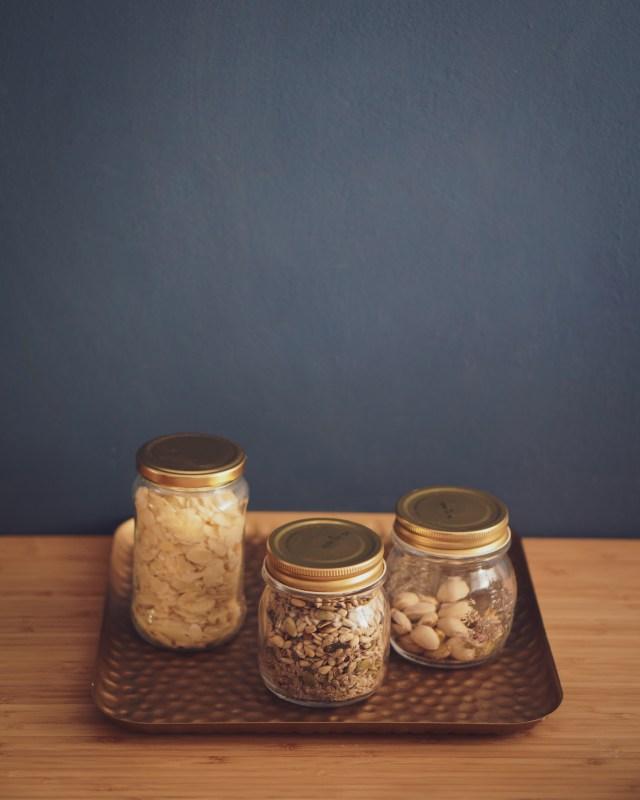 Migdały, orzechy i pistacje w słoikach na złotej tacy