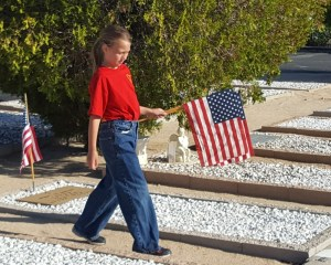 Christyona Lang puts flags on graves at the 29 Palms Cemetery in preparation for the Memorial Day ceremony.