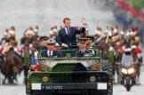New French President Emmanuel Macron waves from a military vehicle as he rides on the Champs Elysees avenue towards the Arc de Triomphe in Paris, France, Sunday, May 14, 2017. (AP Photo/Michel Euler, POOL)