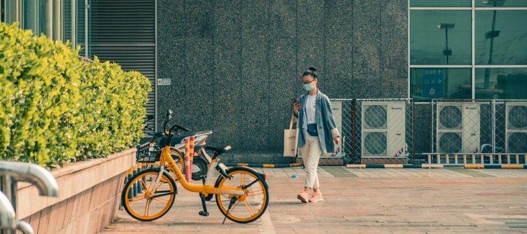woman wearing facemask walking towards the bike stand
