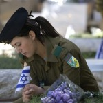 An Israeli soldier places a national flag on grave of a fallen comrade in Jerusalem