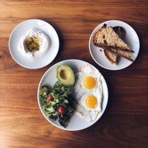 Breakfast Platter w/ sunny side up eggs, green salad, avocado, labane, and sourdough bread.