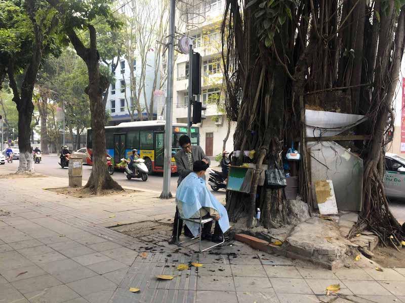 Homem corta o cabelo na rua
