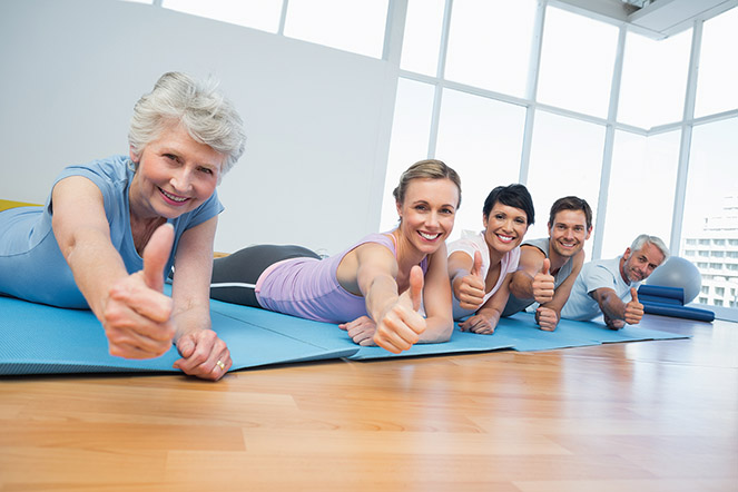 Fitness group gesturing thumbs up in row at the yoga class
