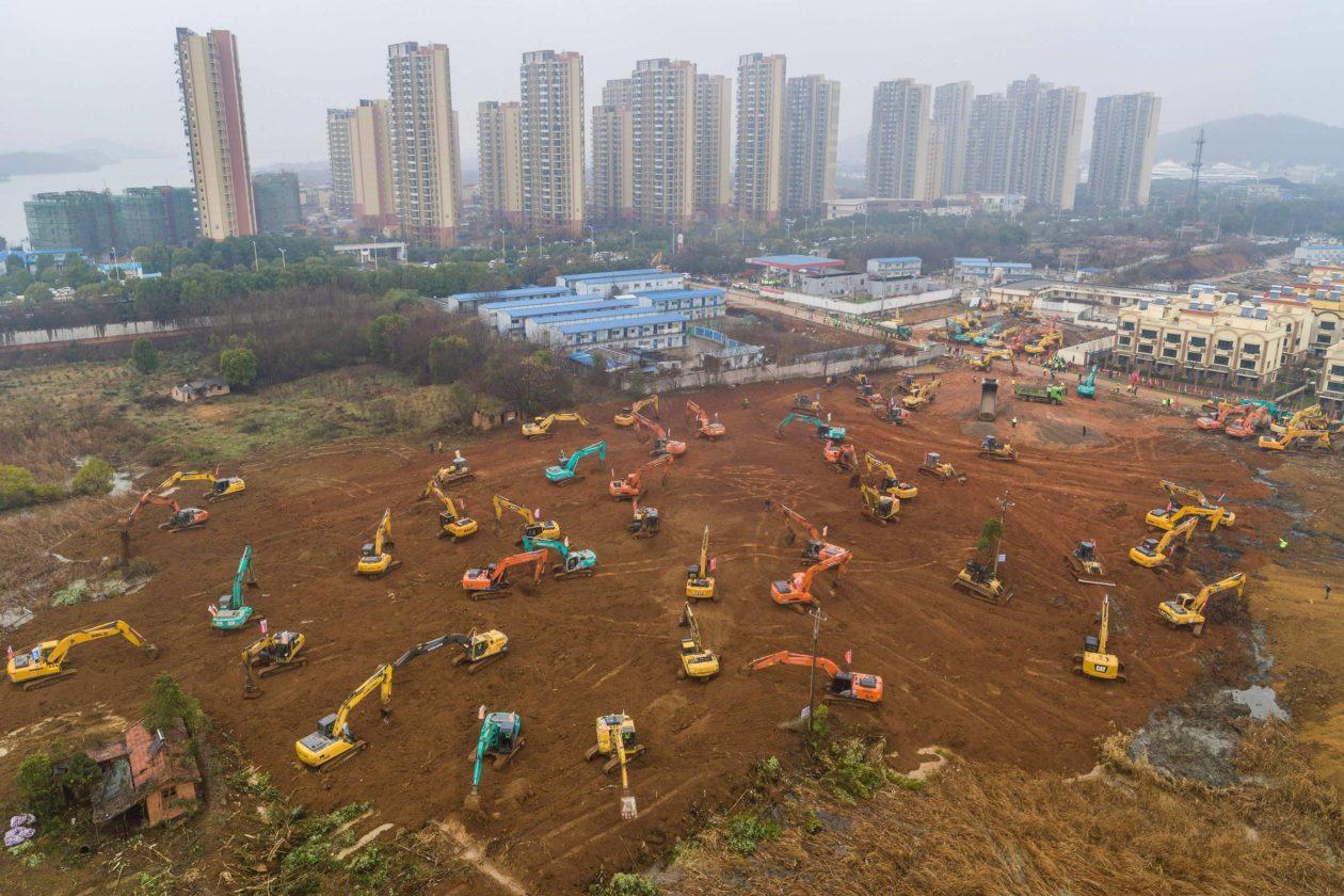 Tratores escavando para a construção de hospital na cidade de Wuhan