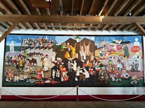 Mural w sali muzealnej przedstawiający całą działalność fabryki.