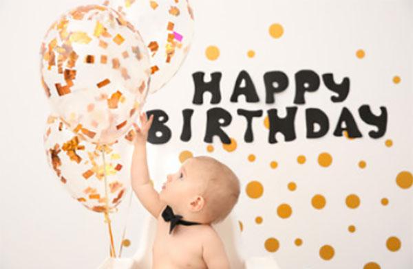 """Ребенок тянется к воздушным шарам, сверху надпись """"Happy birthday"""""""