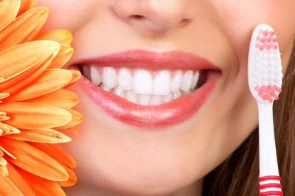 Beautiful woman smile, teeth and a fresh flower