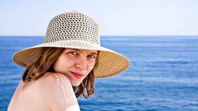 жена с лятна шапка на плаж