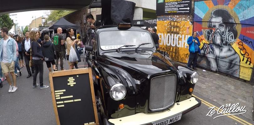 Vendeur de café dans un taxi noir Londonien au marché de Bricklane.