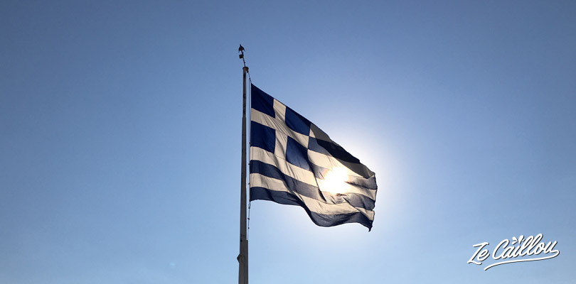 Greek flag flying in the wind of Acropolis in Athens, perfect holidays in Greece.